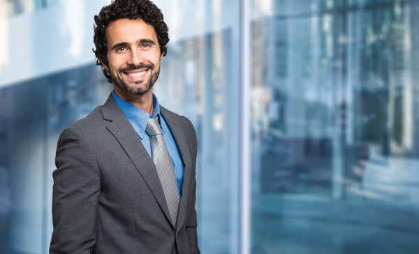 Portrait of a smiling businessman in front of a blue modern back